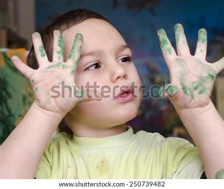 Portrait of a child boy  painting a colorful abstract picture with a brush and poster paint colors. - stock photo