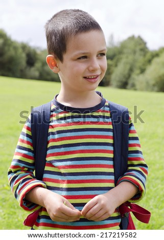 Portrait of a child boy standing on a meadow on a nature walk.