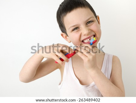 Portrait of a child boy with a gap in his teeth brushing his teeth with a tooth brush - stock photo