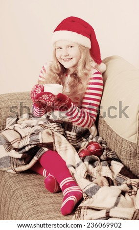 Portrait of a child drinking hot tea in Santa hat - stock photo