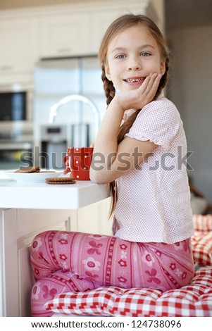 Portrait of a child having breakfast at the kitchen at home