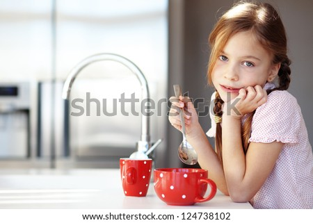 Portrait of a child having breakfast at the kitchen at home - stock photo