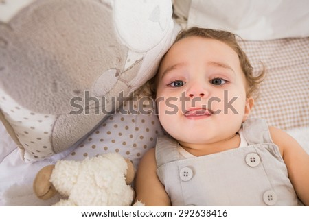 Portrait of a child in hid bed with pillow at home in bedroom - stock photo
