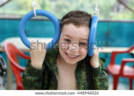 Portrait of a child on gymnastic rings - stock photo