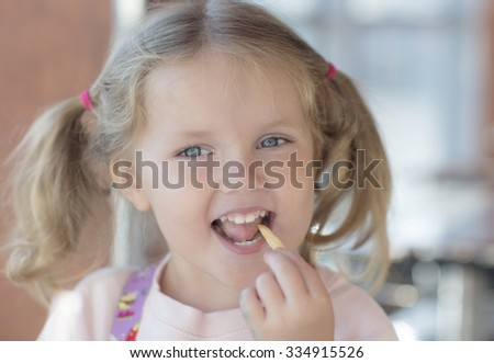 Portrait of a child with hairstyle. Girl eating fries and smiles.