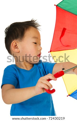 Portrait of a Chinese boy playing with umbrella isolated over white