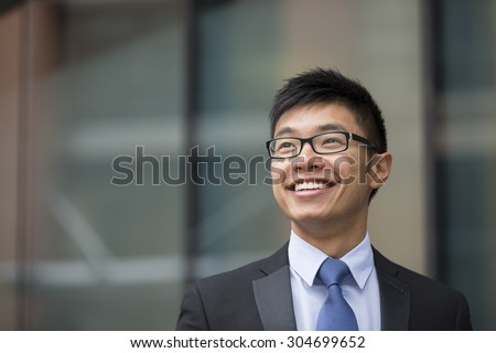 Portrait of a Chinese businessman outside modern office building, looking away. - stock photo
