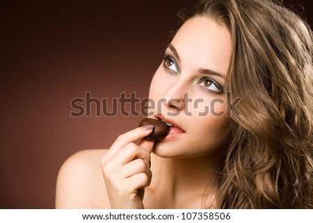 Portrait of a chocolate loving young brunette beauty - stock photo