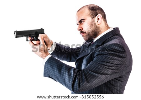 portrait of a classy businessman or mobster or security guard holding a gun isolated over a white background - stock photo