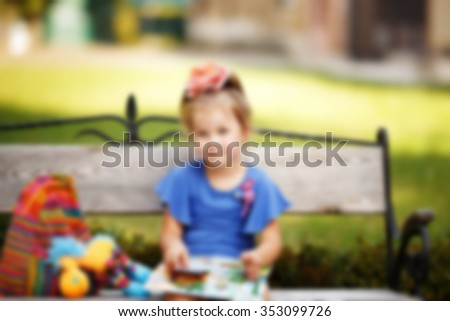 Portrait of a clever little girl reading a children's book on a park bench, blured - stock photo