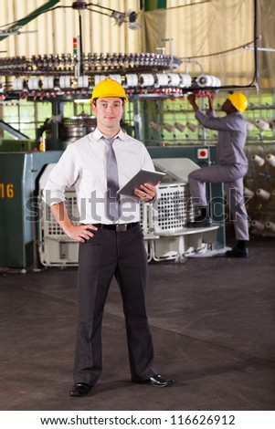 portrait of a cloth manufacturing factory manager with tablet computer - stock photo