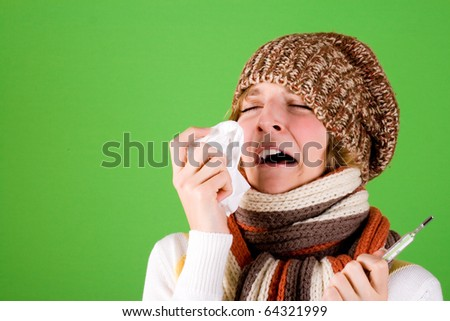 portrait of a cold girl sneezes with handkerchief and thermometer on green background - stock photo