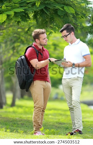 portrait of a college student explaining a subject to his friend at college park - stock photo