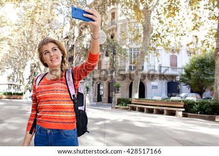 Portrait of a college student holding a smart phone device, taking pictures of a destination city on holiday, sunny outdoors. Travel lifestyle and technology. Young woman using cell phone, exterior. - stock photo