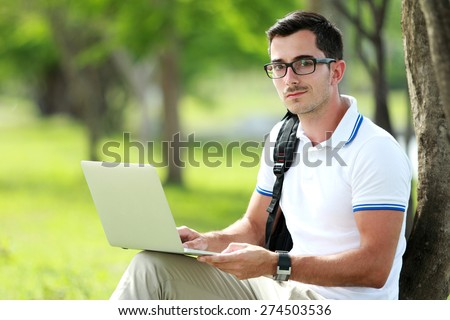 portrait of a college student looking at camera while working an assignment on his laptop under the tree - stock photo