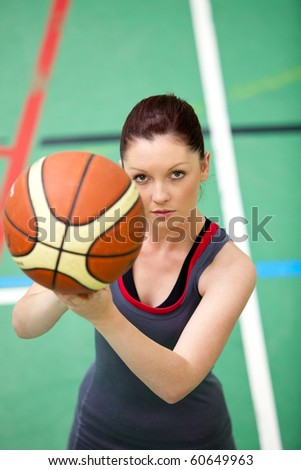 Portrait of a concentrated young woman playing basket-ball in a gymnasium - stock photo
