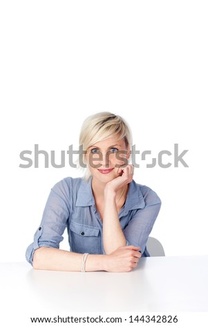 Portrait of a confident blond woman with hand on chin sitting at table against white background - stock photo