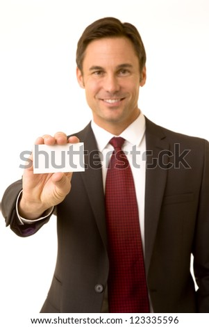 Portrait of a confident business executive holding up a business card, shallow focus with focus on card - stock photo