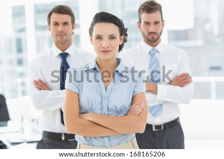 Portrait of a confident business team standing with arms crossed in a bright office