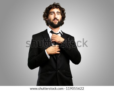 Portrait Of A Confident Businessman against a grey background - stock photo