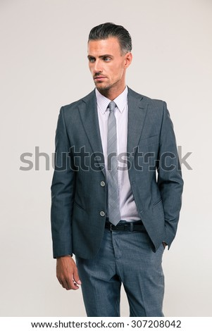 Portrait of a confident businessman standing isolated on a white background and looking away - stock photo