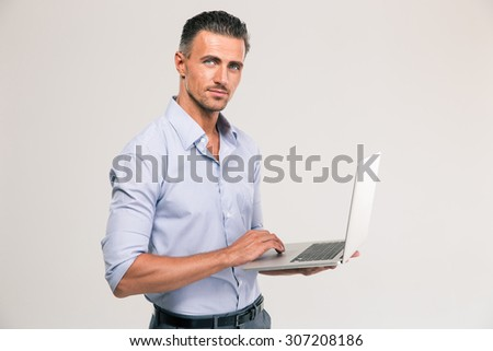 Portrait of a confident businessman using laptop and looking at camera - stock photo