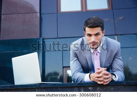 Portrait of a confident businessman with laptop computer outdoors. Looking at camera - stock photo