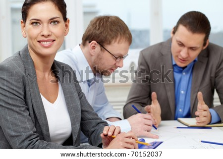 Portrait of a confident businesswoman against her working colleagues - stock photo