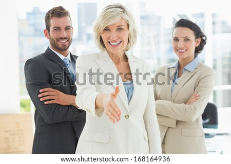 Portrait of a confident businesswoman offering handshake with team in a bright office - stock photo