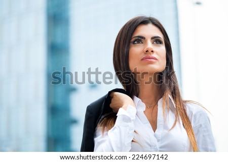 Portrait of a confident businesswoman walking in a city - stock photo