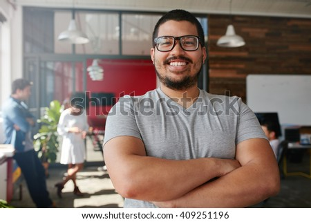 Portrait of a confident creative professional with colleagues in the background. Mixed race man standing with his arms crossed looking at camera and smiling. - stock photo
