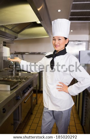 Portrait of a confident female cook standing in the kitchen