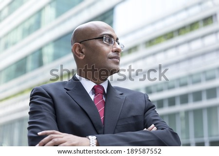 Portrait of a confident Indian Business man standing in modern city. Business man looking away from camera. - stock photo