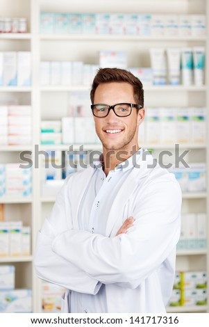 Portrait of a confident male pharmacist smiling in front of medicines at drugstore - stock photo