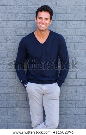Portrait of a confident man smiling against gray wall - stock photo