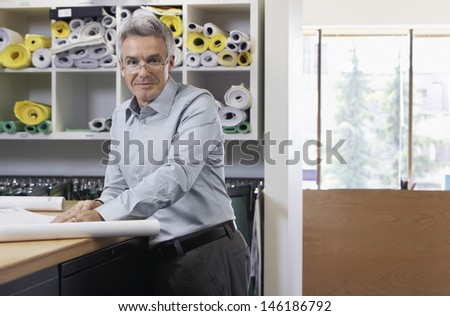 Portrait of a confident middle aged man with paperwork in office