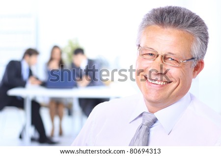 Portrait of a confident senior business man at meeting colleagues sitting at the back - stock photo