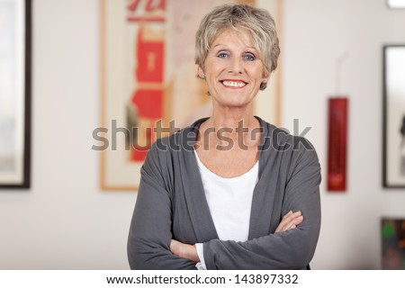 Portrait of a confident smiling senior woman standing with arms crossed at home - stock photo