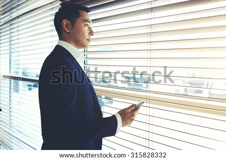 Portrait of a confident young businessman holding cell telephone while standing near office window, intelligent men in elegant suit waiting for a call on his mobile phone while resting after meeting - stock photo
