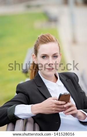 Portrait of a confident young businesswoman with mobile phone sitting in city park bench - stock photo