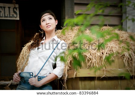 Portrait of a confident young cowgirl standing beside thatch loo - stock photo