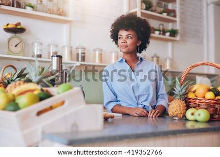 Portrait of a confident young female employee standing at the juice bar counter. African woman working at juice bar and looking away.