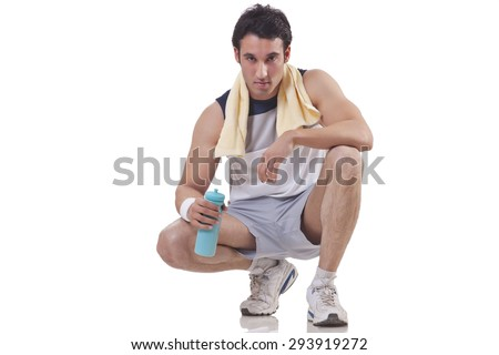 Portrait of a confident young man with a bottle and a towel around neck over white background - stock photo
