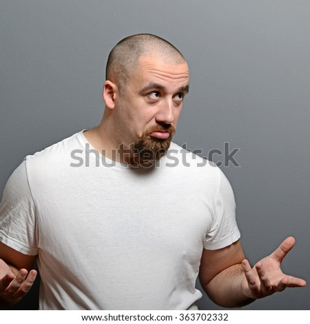 Portrait of a confused man against gray background - stock photo