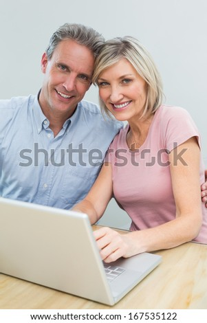 Portrait of a content casual couple using laptop at home