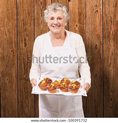 portrait of a cook senior woman holding a chocolate muffins tray against a wooden wall - stock photo
