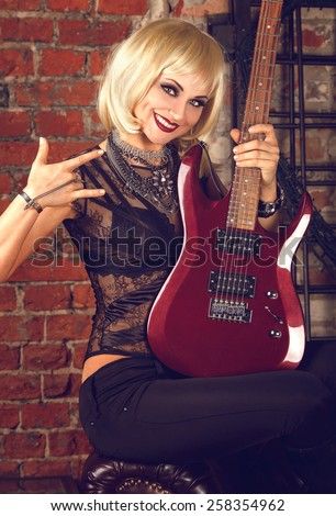 Portrait of a cool glam rock blonde sexy woman in black lingerie with red guitar on a brick wall background - stock photo
