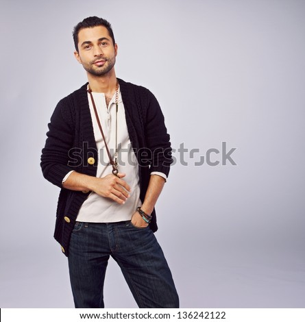 Portrait of a cool guy standing in a studio - stock photo