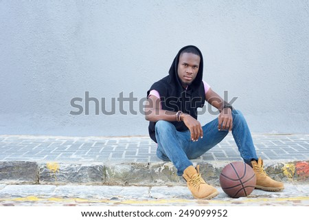 Portrait of a cool young guy sitting on sidewalk with basketball - stock photo