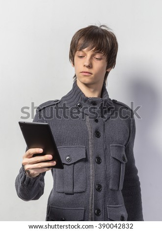 Portrait of a cool young guy standing in casual clothes, holding on digital tablet while standing on white background - stock photo